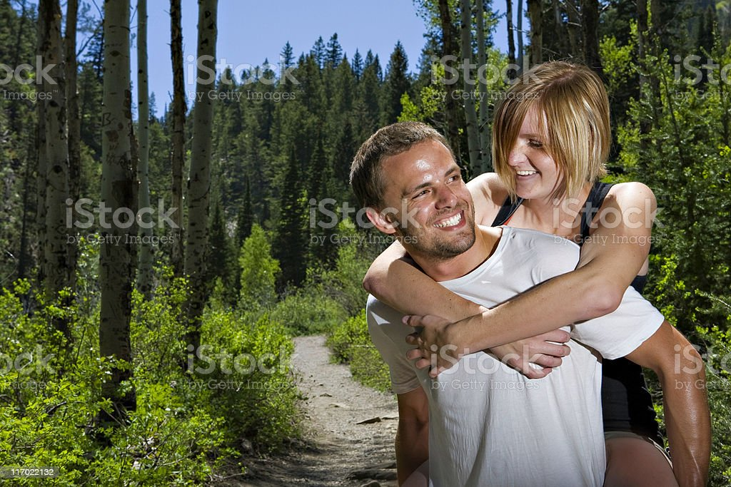 Young girl with boy piggyback laughing while hiking royalty-free stock photo