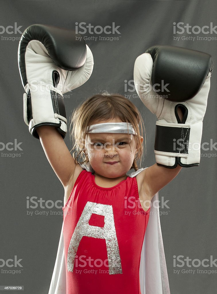 Young Girl With Cape and Boxing Gloves stock photo