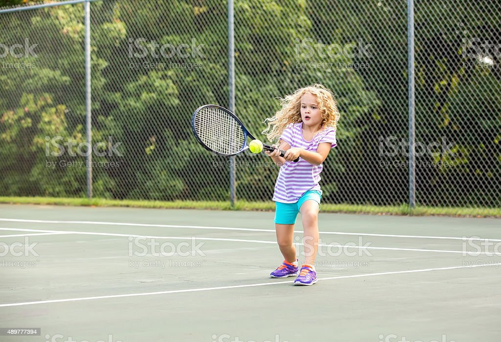 Young Girl With Curly Blonde Hair Practicing Tennis stock photo