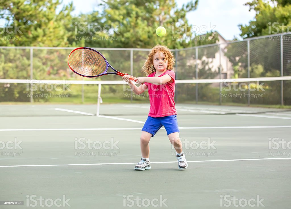 Young Girl With Curly Red Hair Playing Tennis stock photo