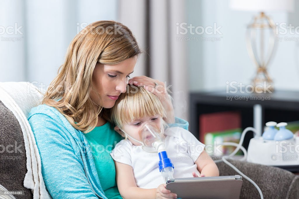 Young girl with cystic fibrosis receives breathing treatment stock photo