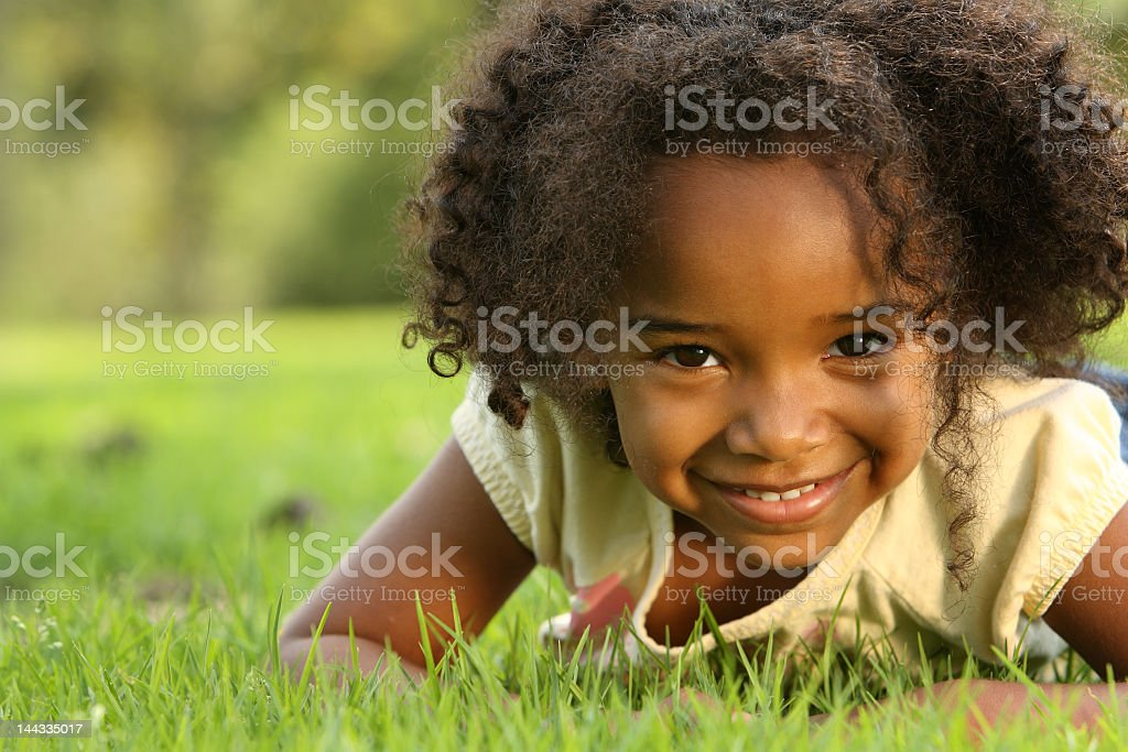 Young girl with dark skin lying down in a field stock photo