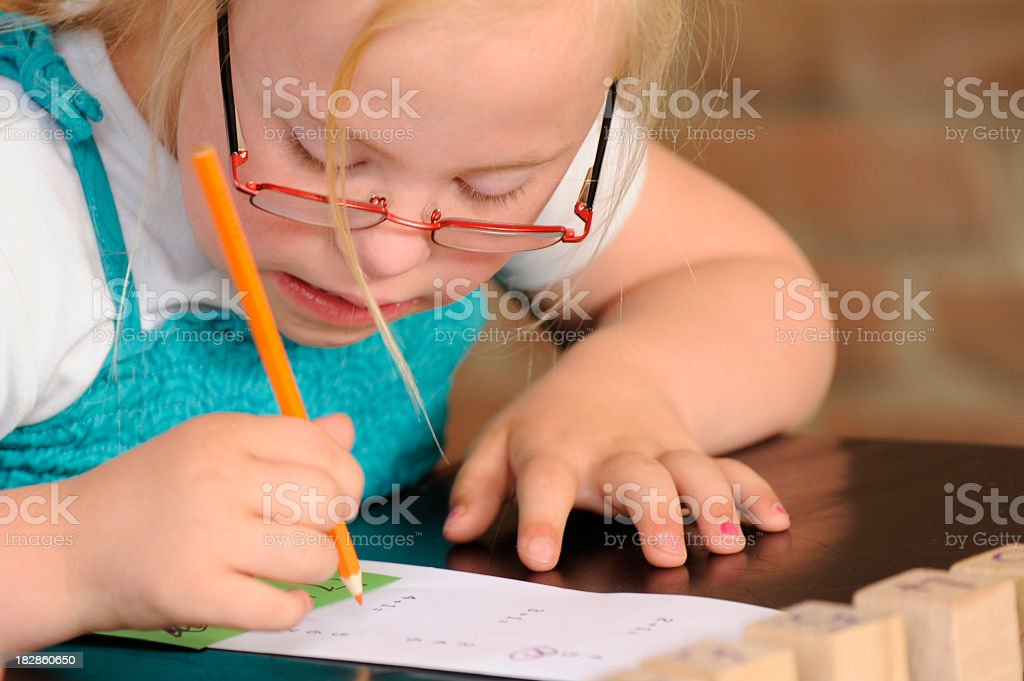 Young girl with Down syndrome writing on paper royalty-free stock photo