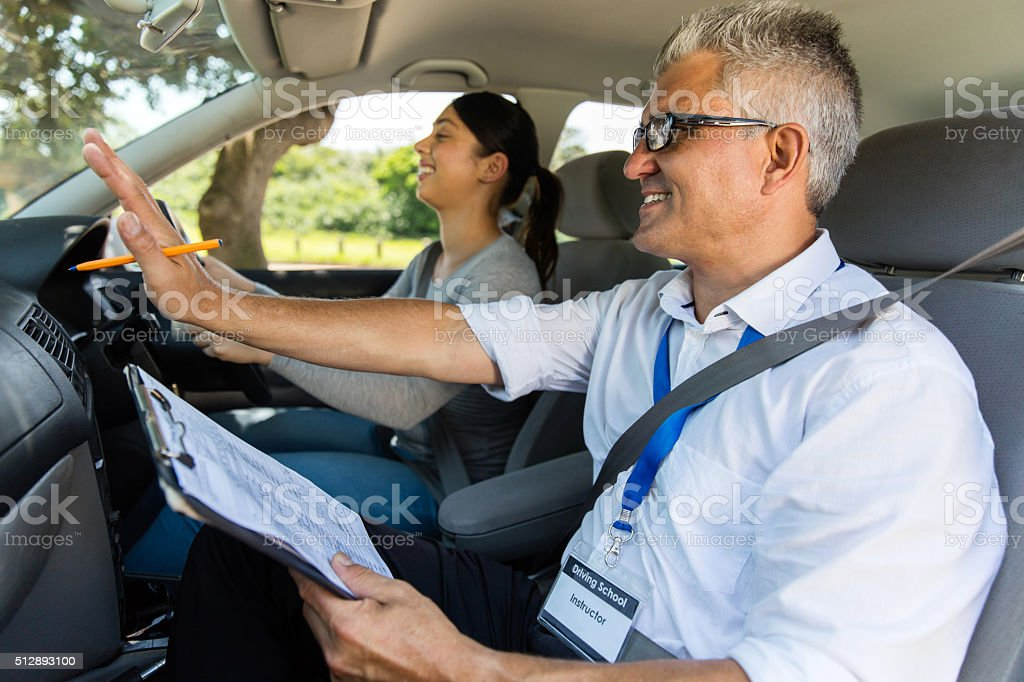 young girl with driving instructor taking lessons stock photo