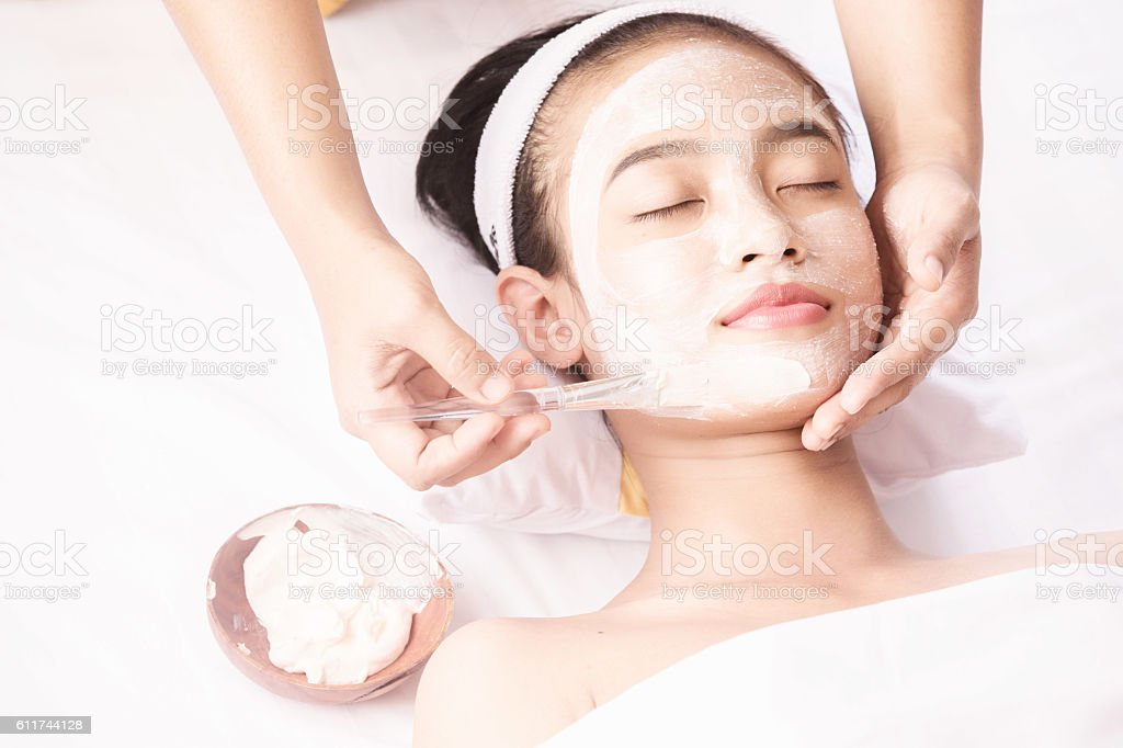 Young girl with facial mask at beauty salon stock photo