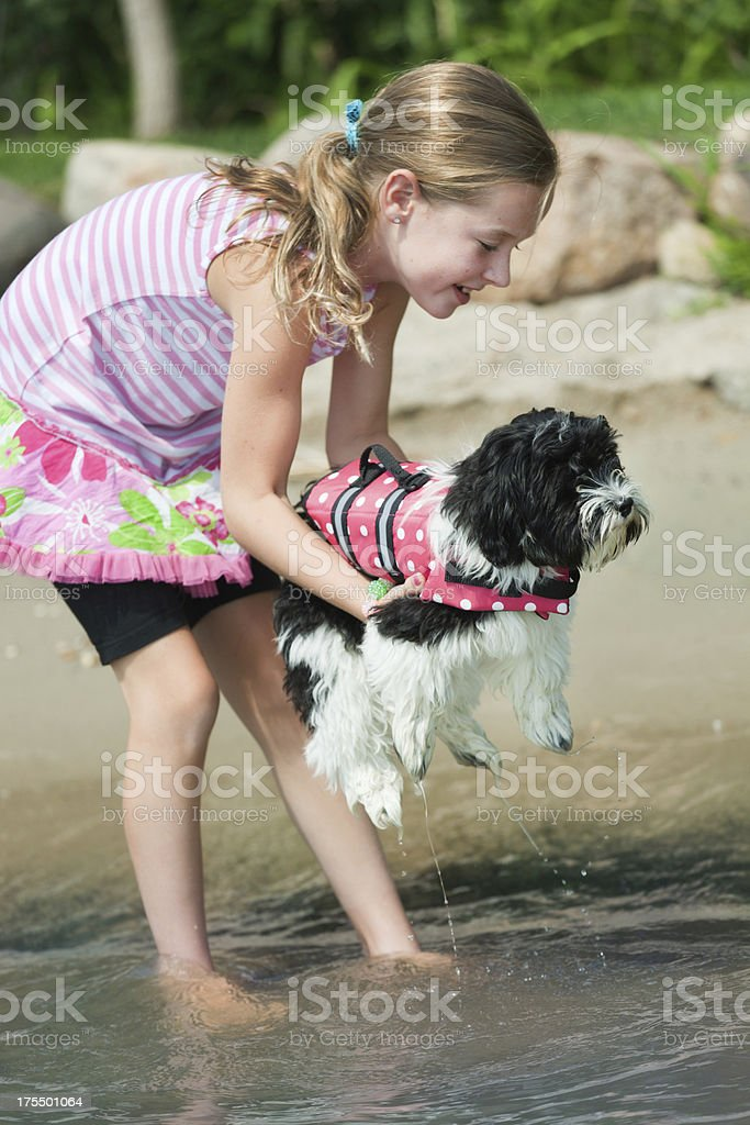 Young Girl with Family Pet Puppy by a Lake royalty-free stock photo