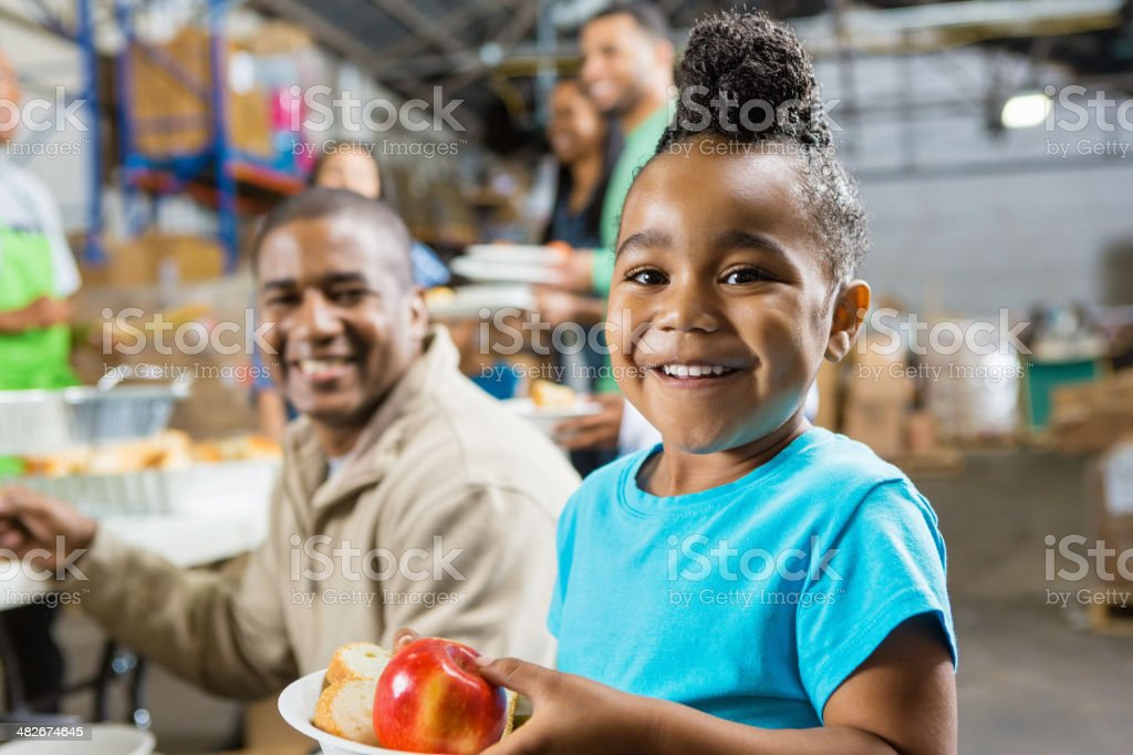 Young girl with father eating healthy food at soup kitchen stock photo