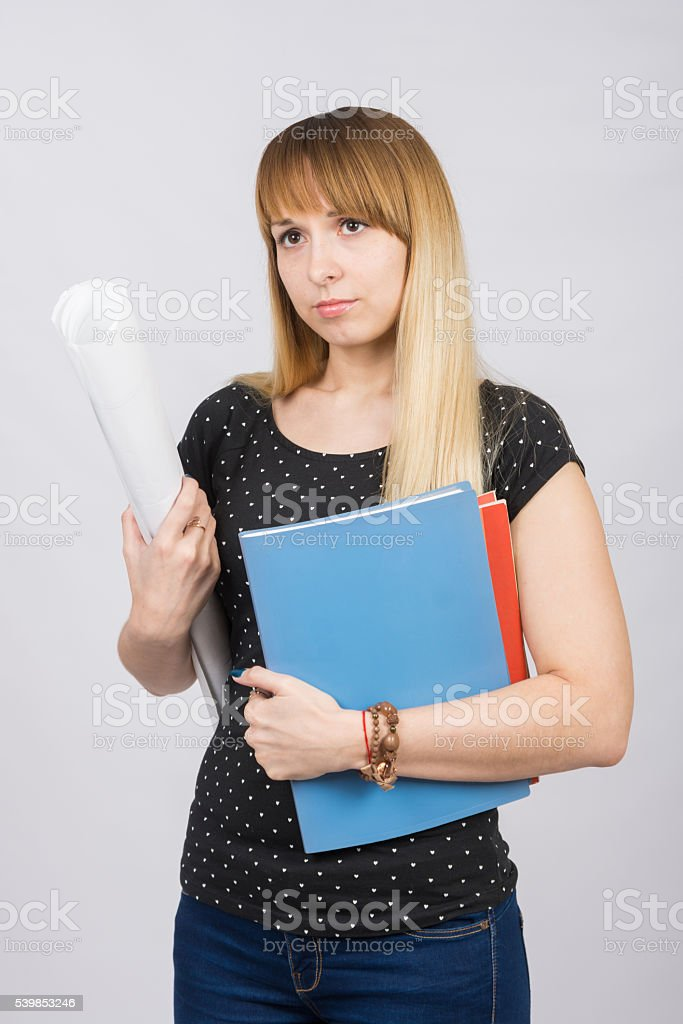 Young girl with folders and roll of paper in hands stock photo