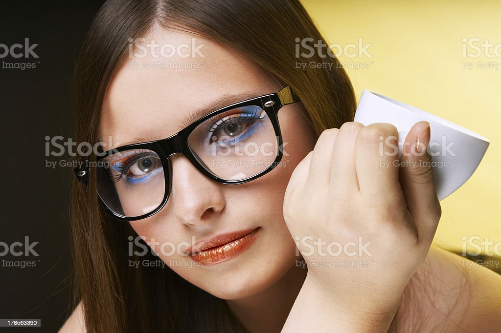 Young girl with glasses and cup on a yellow background royalty-free stock photo