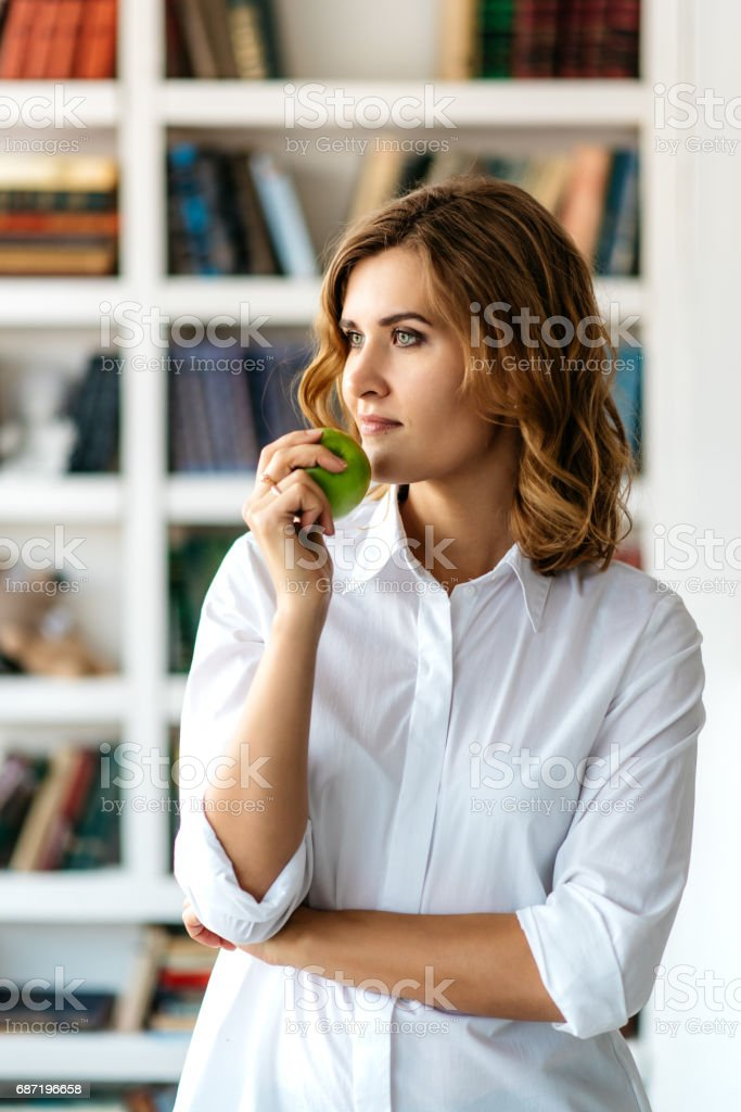 Young girl with green apple in hand stock photo