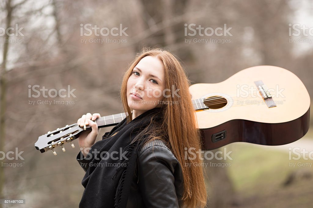 Young girl with guitar looking in camera, travel concept stock photo