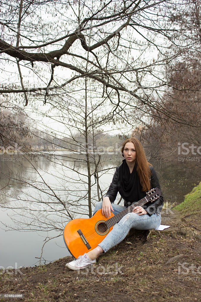 Young girl with guitar  sitting on the ground,, travel concept stock photo