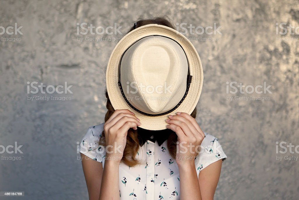 Young girl with hat. Hides her face.Depression. stock photo
