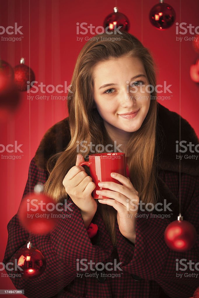 Young woman with a warm drink in a Christmas theme background.