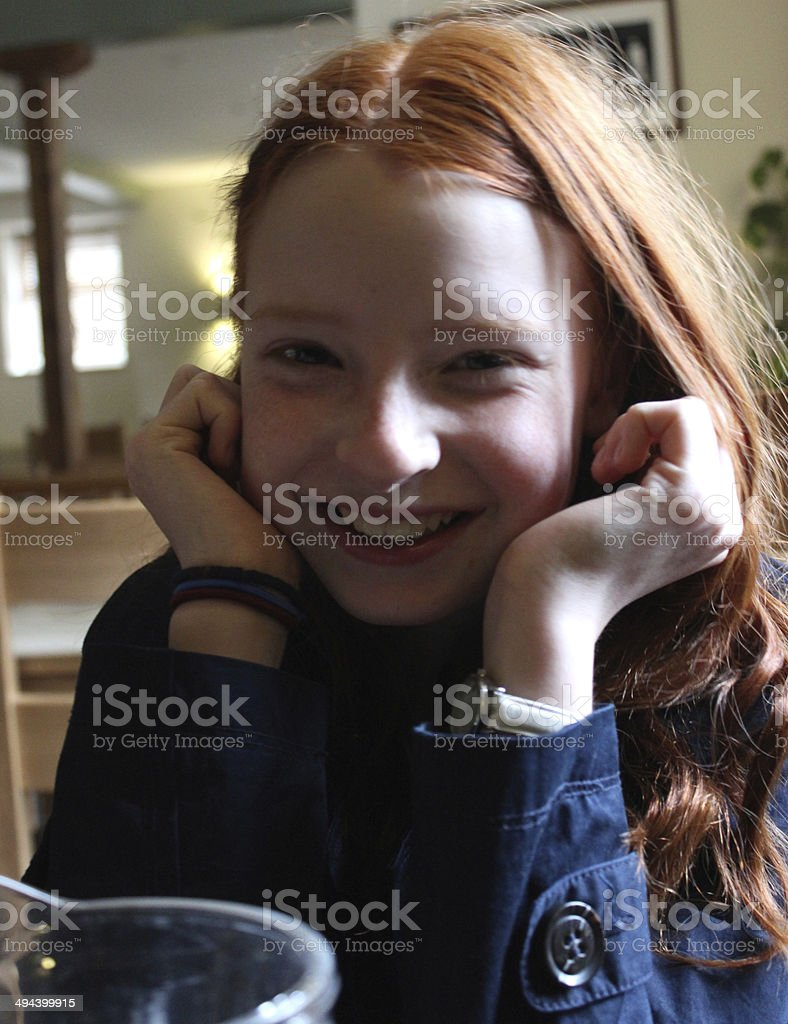 Young girl with long red hair, giggling, smiling and posing stock photo