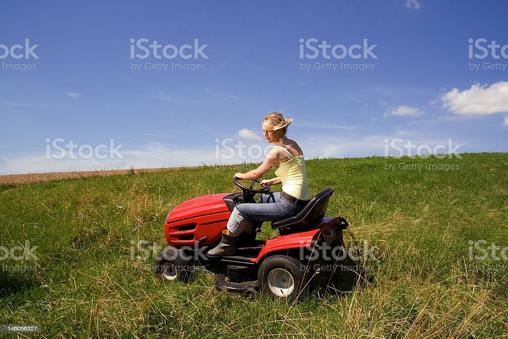 young girl with mowing machine stock photo