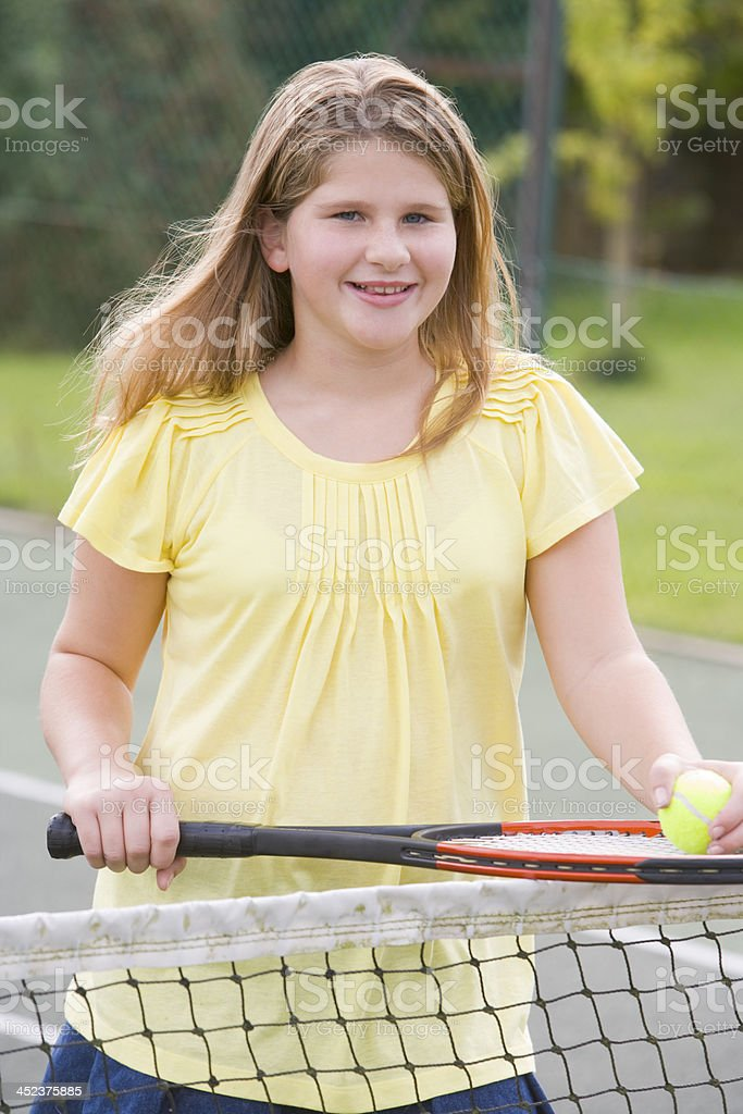 Young girl with racket on tennis court smiling royalty-free stock photo