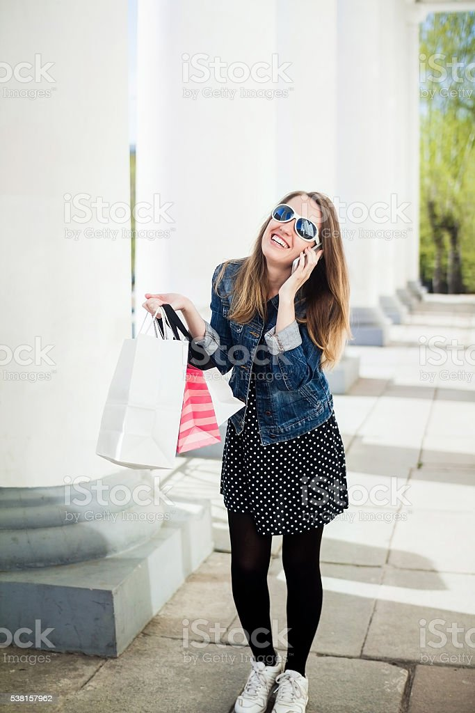 Young girl with shopping bags talking on cellphone stock photo