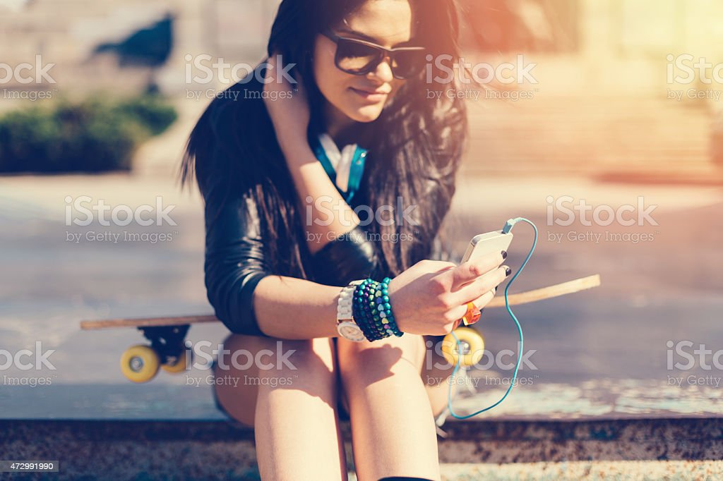 Young girl with skateboard texting on smartphone stock photo