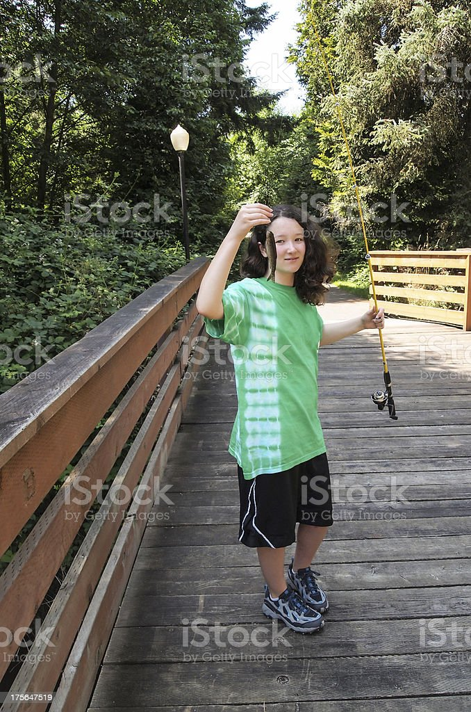 Young girl with Small Fish on Wooden Bridge royalty-free stock photo