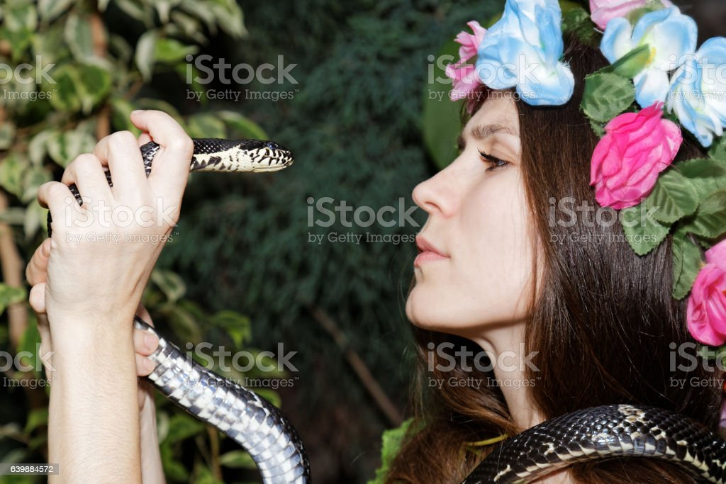 Young girl with snake. Temptation of Eve. stock photo