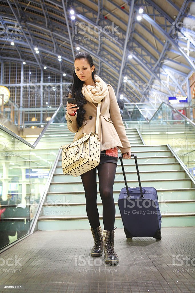 Young girl with suitcase at railway station stock photo