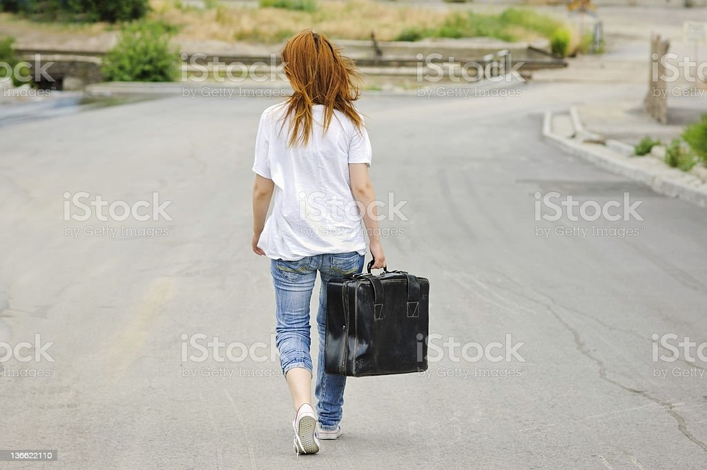 Young girl with suitcase walking down the street. Rear view royalty-free stock photo