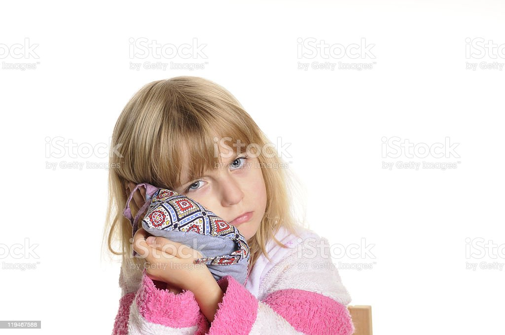 Young girl with white and pink robe holds a pillow to face stock photo