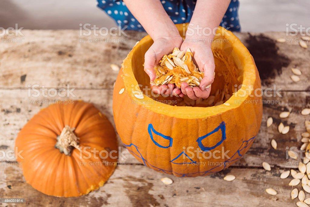 Young Girl Working On Her Halloween Pumpkin stock photo