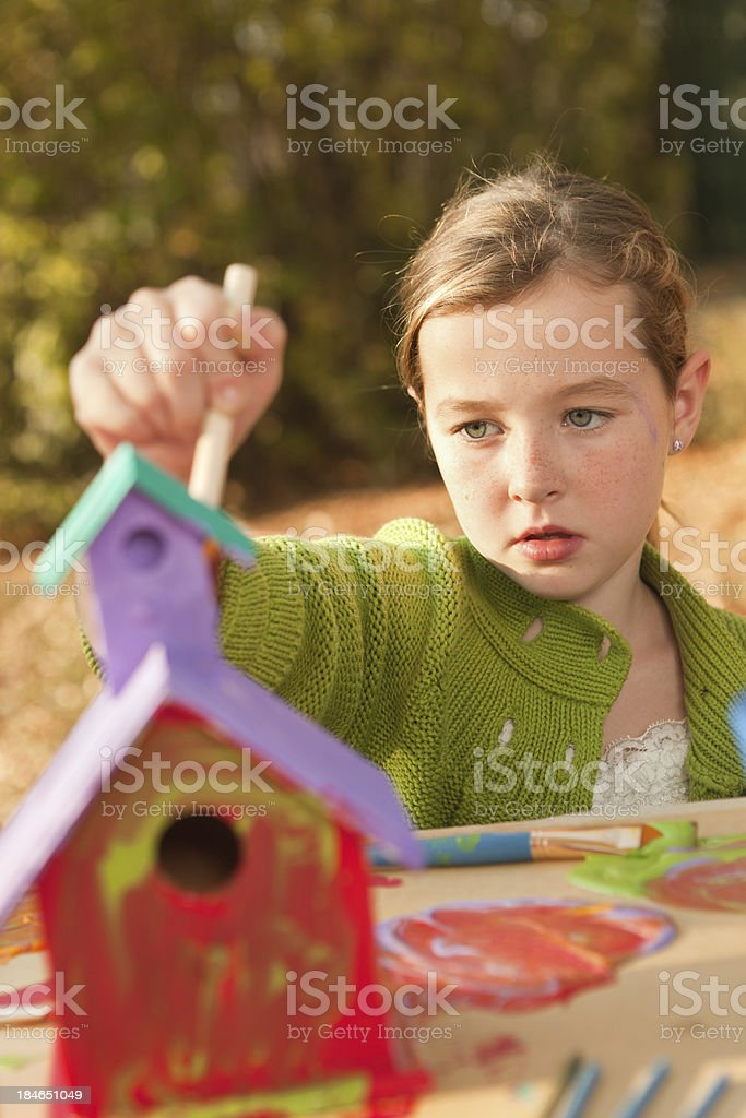 Young Girl Working on Painting Birdhouse royalty-free stock photo