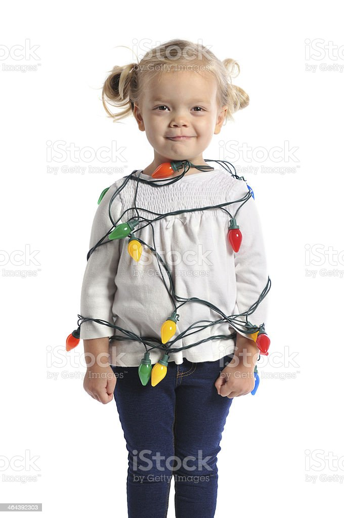 Young Girl Wrapped in Multicolored Christmas Tree Lights royalty-free stock photo