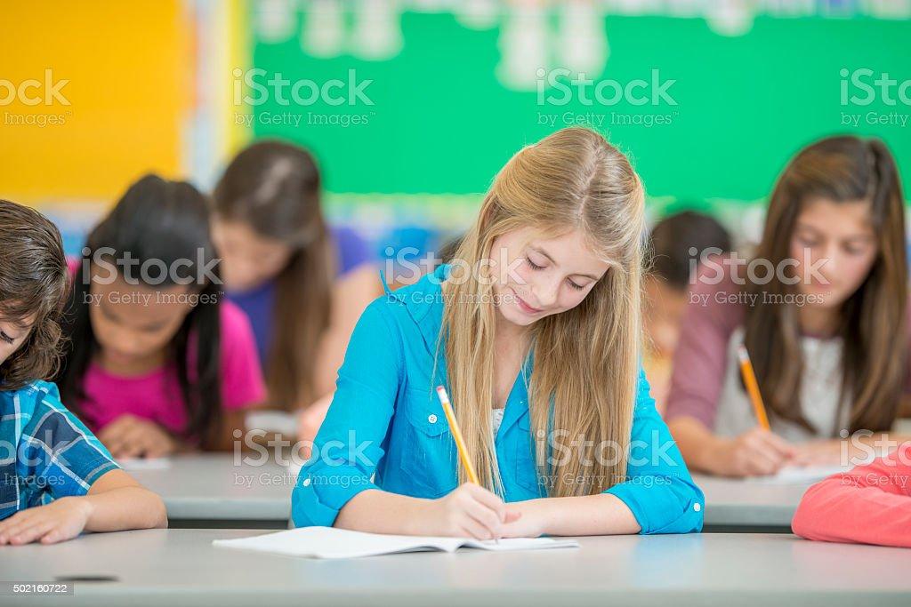 Young Girl Writing an Exam stock photo
