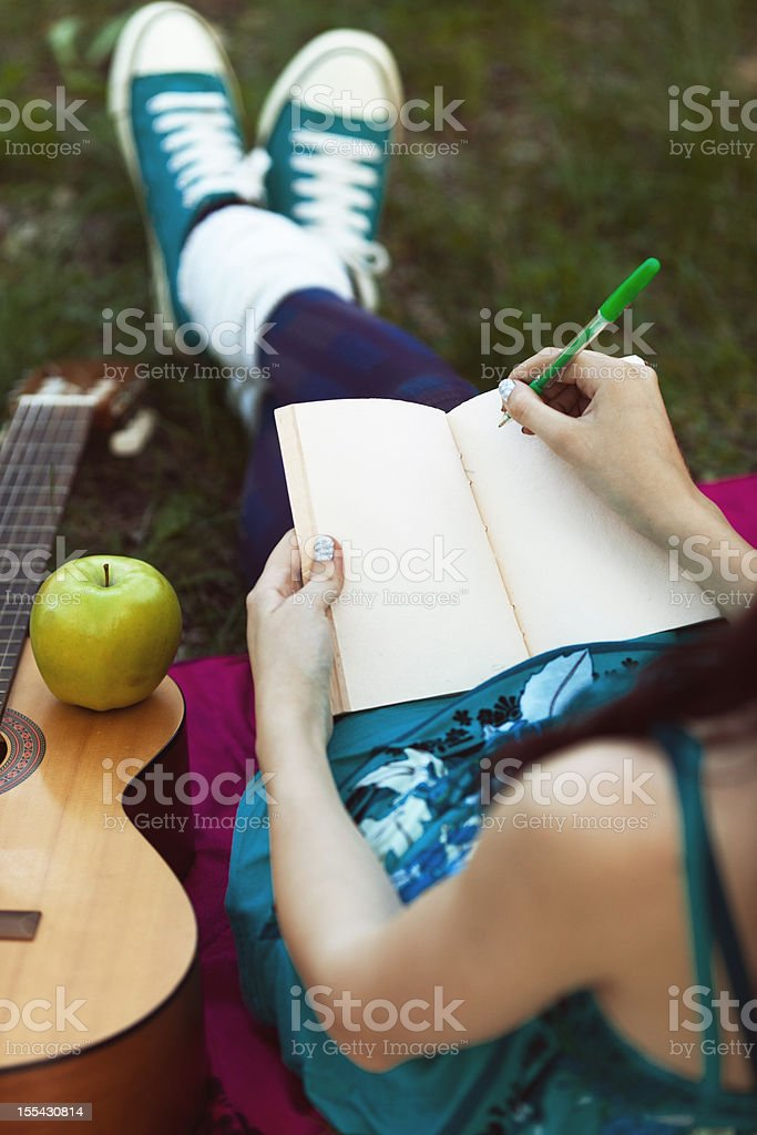 young girl writing in notebook stock photo