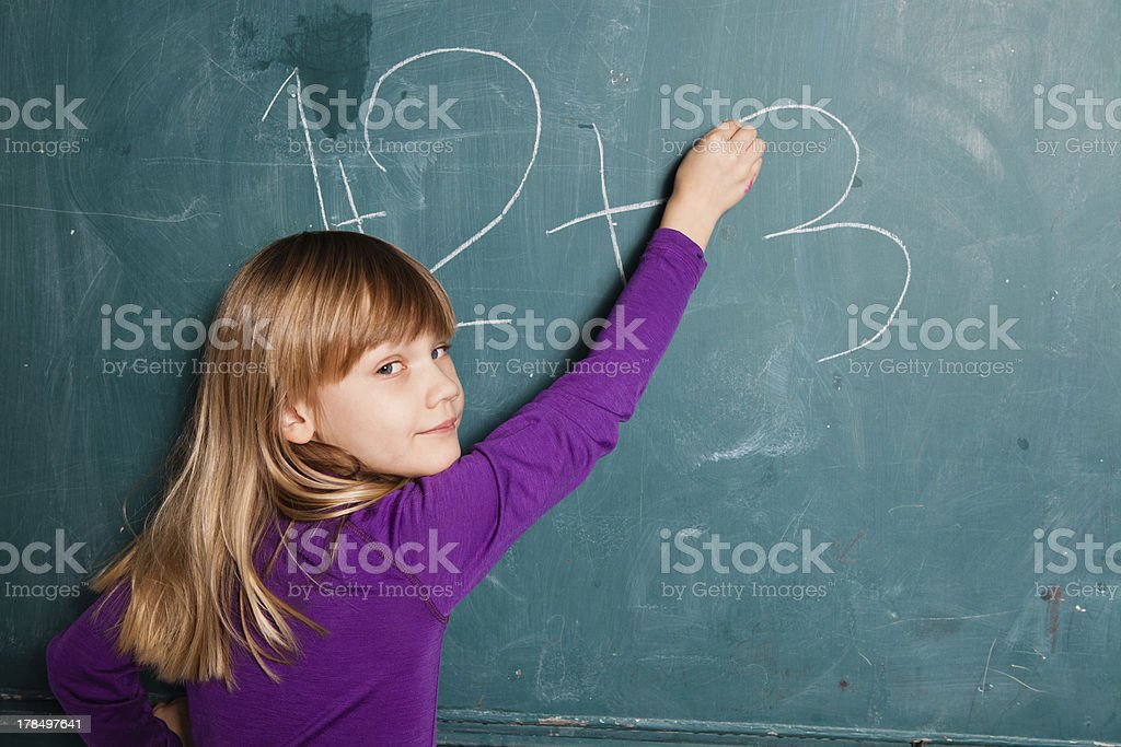 Young girl writing numbers on chalkboard royalty-free stock photo