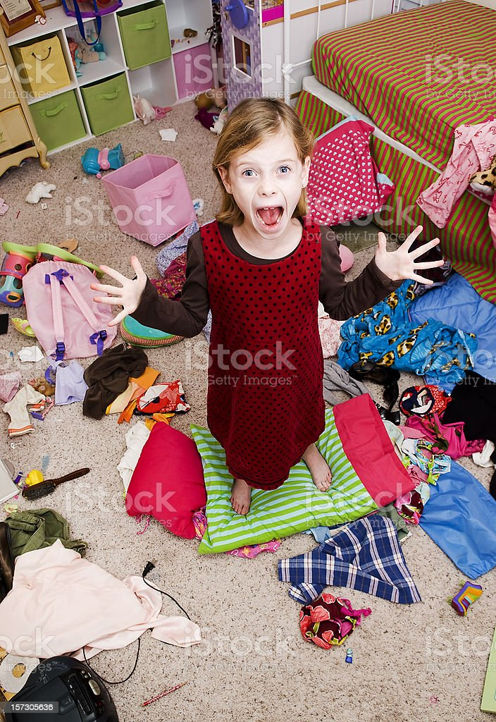 Young girl yelling in very messy bedroom  stock photo