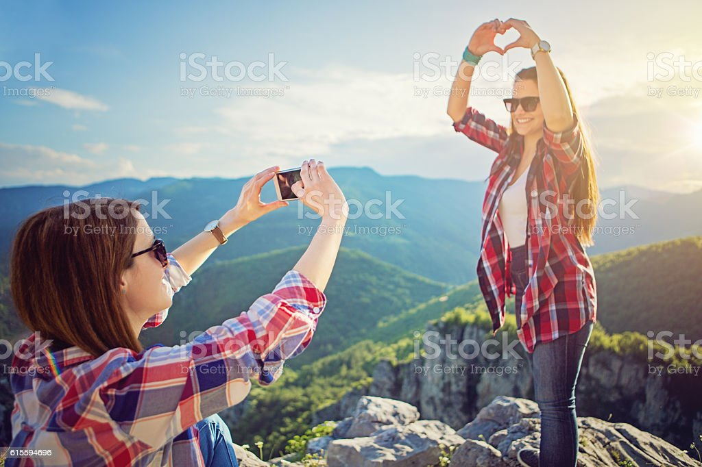 Young girls are taking pictures at the front of sunset stock photo