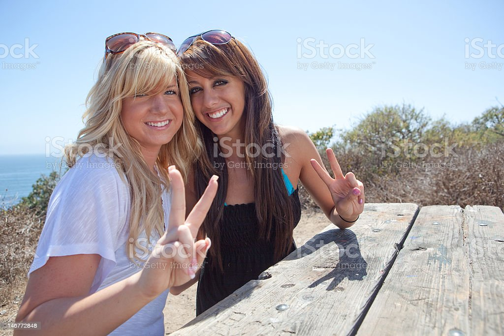 Young Girls at Beach showing peace sign on Vacation royalty-free stock photo
