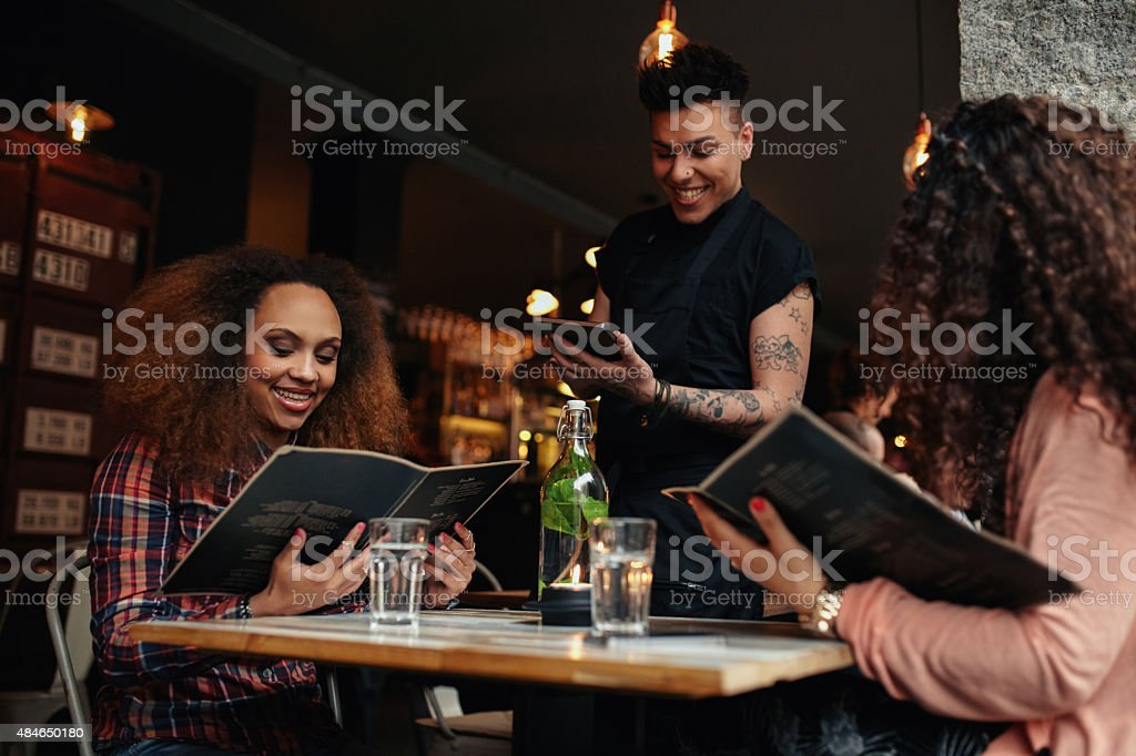 Young girls at cafe giving order to the waiter stock photo