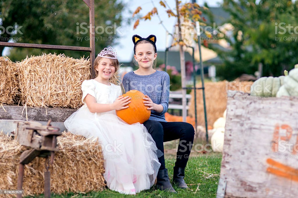 Young girls dressed up for halloween holidng a pumpkin stock photo