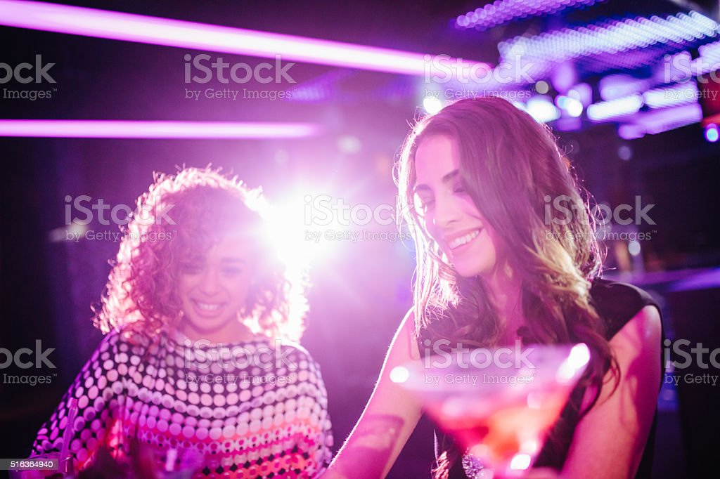 Young girls drinking cocktail in a night club stock photo