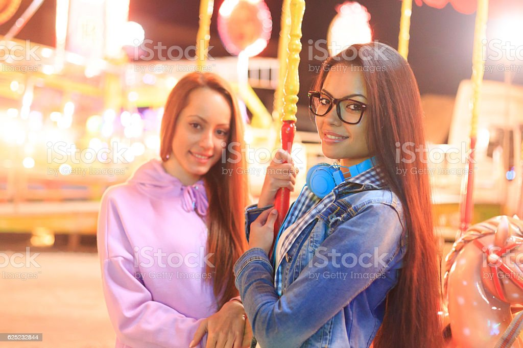 Young girls having fun on marry-go-round in amusement park stock photo