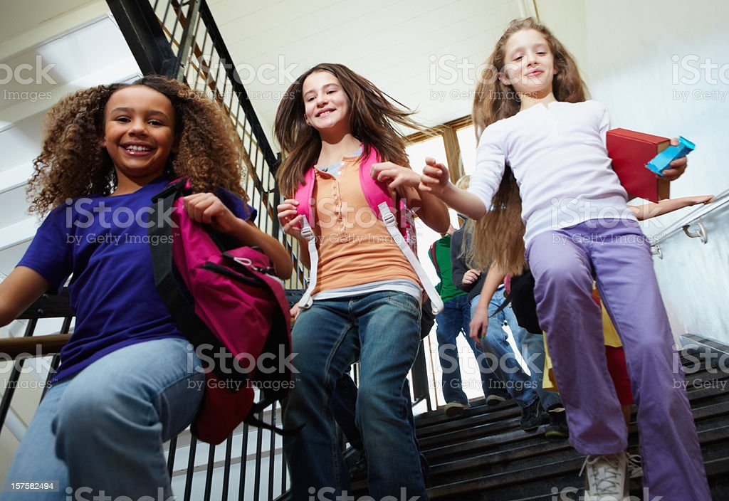 Young girls leaving for home from school stock photo