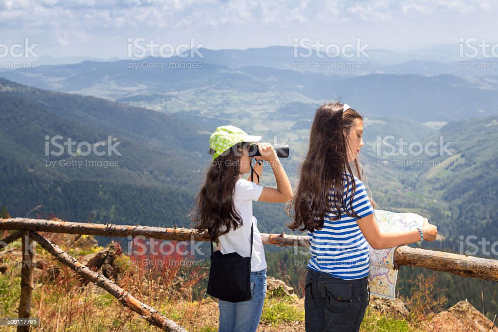 Young girls on the mountain peak using map and binocular stock photo