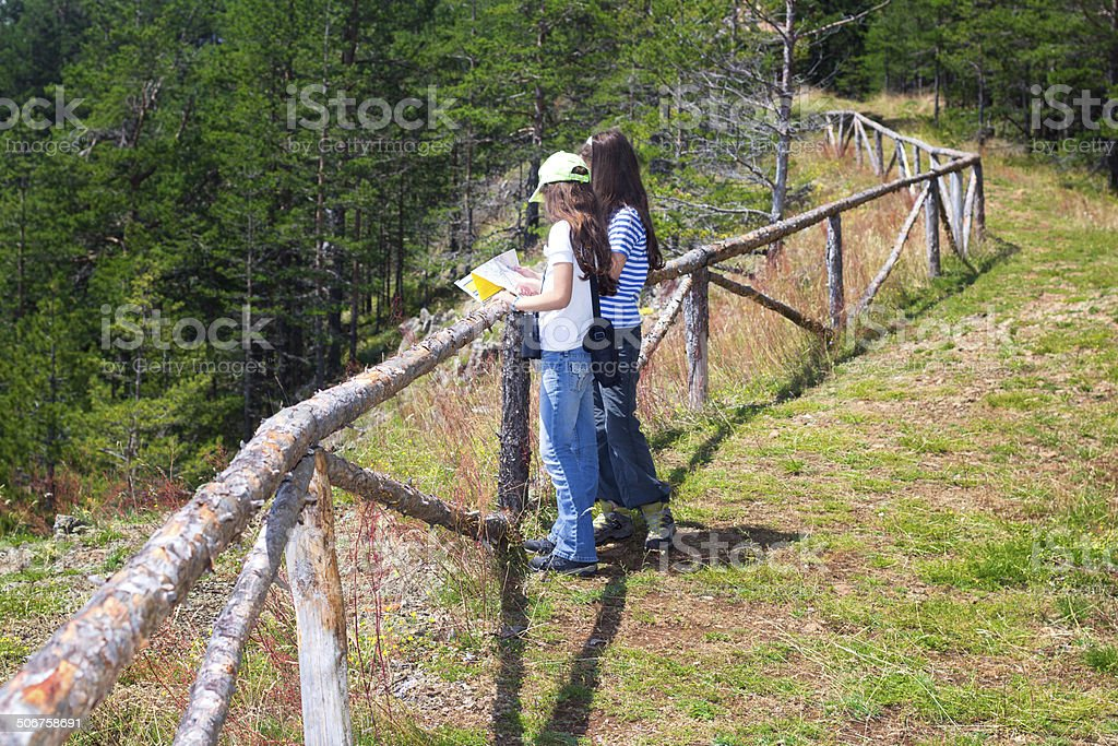 Young girls on the mountain peak using map stock photo