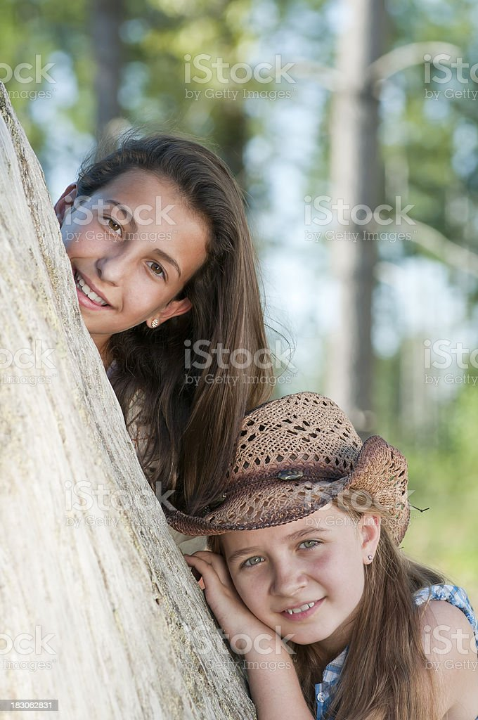 Young girls playing Hide And Seek behind the tree (IV) royalty-free stock photo