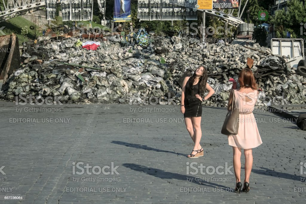 Kiev, Ukraine - August 5, 2014: Young girls posing in front of one of Maidan barricades, a few days before they got dismantled stock photo