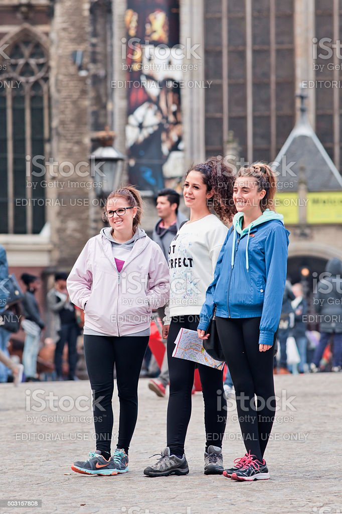 Young girls posing on Amsterdam Dam Square for a photo stock photo