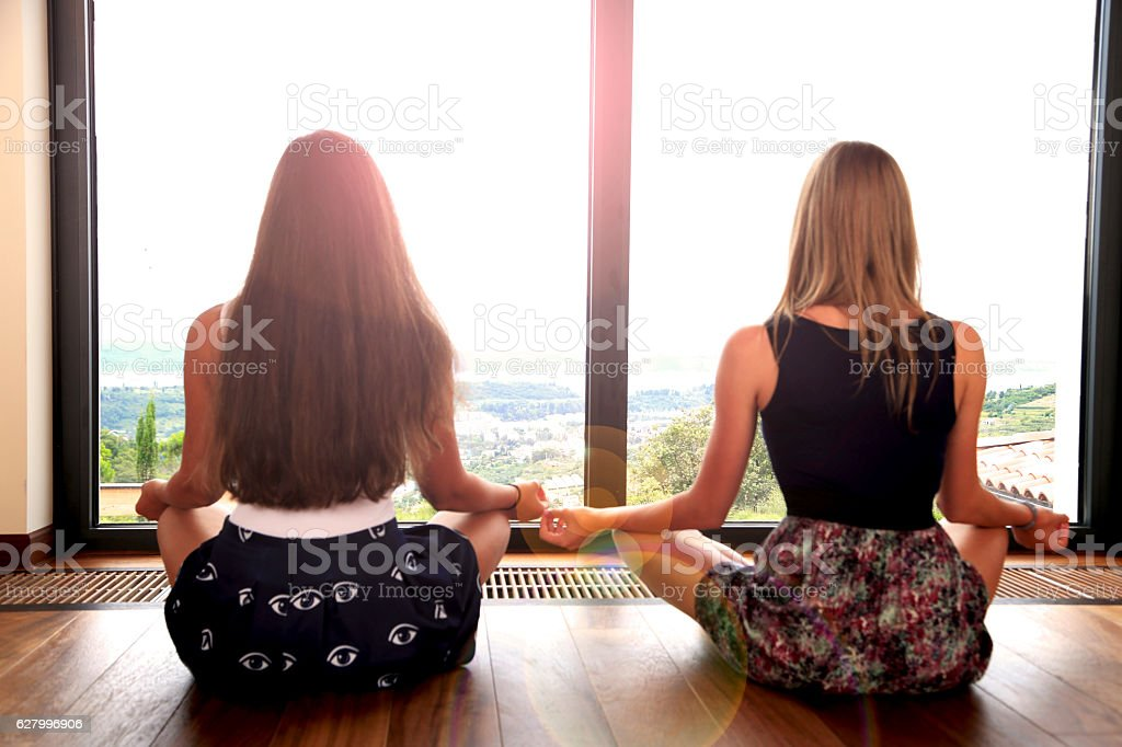 Young girls practising yoga by the window stock photo