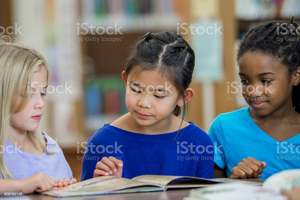 Young Girls Reading Together stock photo