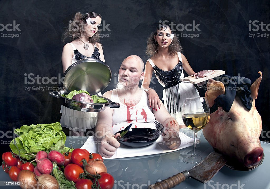 Young girls serving raw pork to a fat man royalty-free stock photo